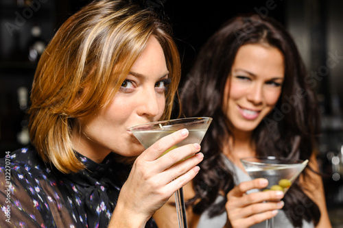 Fotomural Two attractive young women drinking martinis in nightclub bar atmosphere