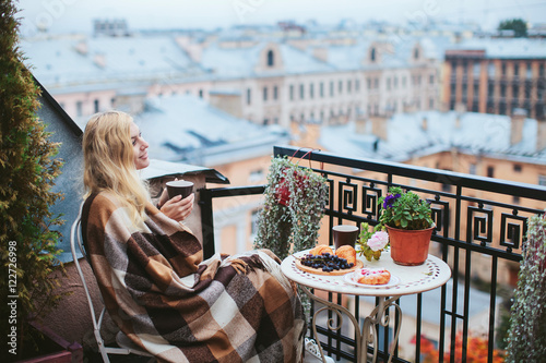 Foto woman with tea sheltered blanket breakfast on the balcony overlooking the city