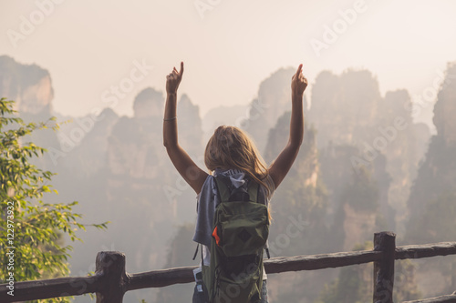 Photo Young woman standing on top of the mountain with view over scenic area of Wulingyuan Park, raising her hands with thumbs up