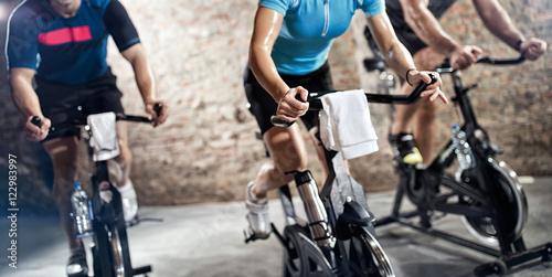 Fototapeta sports clothing people riding exercise bikes