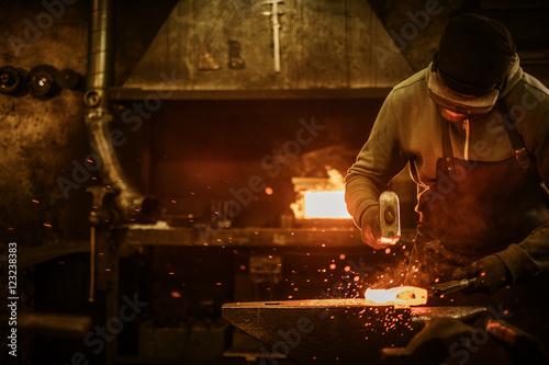 Obraz na płótnie The blacksmith forging the molten metal on the anvil in smithy