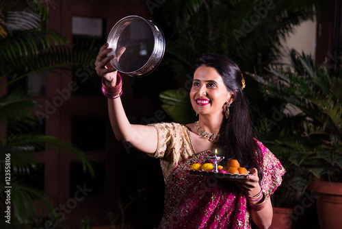 Karva Chauth Hindu woman, smart young indian female or wife performing karvachauth or karwa chauth puja