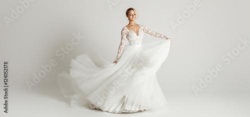 Obraz na płótnie Beautiful attractive bride in wedding dress with long full skirt, white backgrou