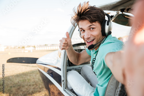 Cheerful pilot sitting in airplane cabin and showing thumbs up Fototapeta