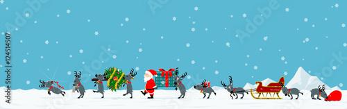 Fotografia Santa and his reindeer are walking among falling snow