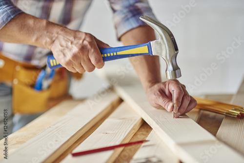 Canvas Print Carpenter with hammer hitting nails.