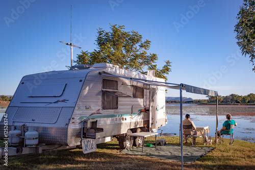 Retired couple with small dog sitting enjoying view to lake alongside modern car Fototapeta
