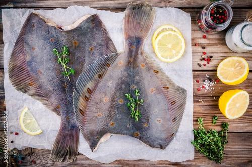 Obraz na plátne Raw flounder fish, flatfish on wooden table