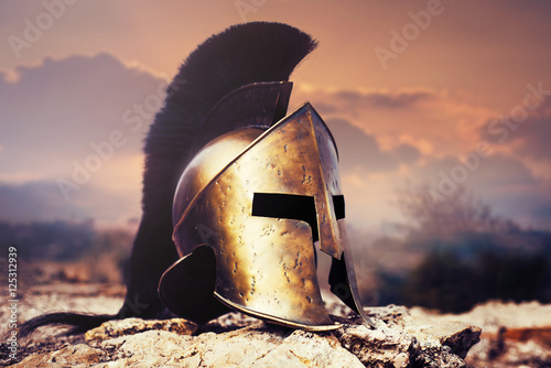 Obraz na plátně Spartan helmet on ruins with sunset sky.