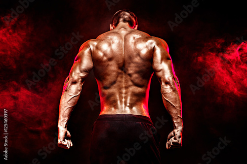 Wallpaper Mural The back view of torso of attractive male body builder on dark smoky background