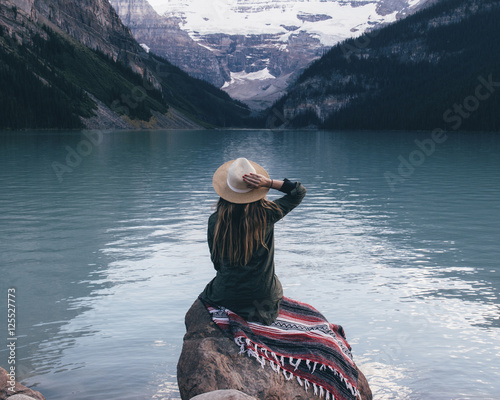 Canvas Print Rear view of woman sitting on rock and looking Lake Louise, Alberta, Canada