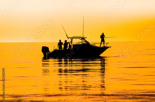 silhouette of sport fishing boat reflecting on calm water Fototapeta