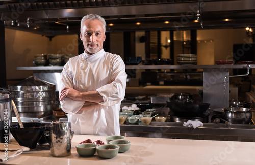 Delighted bearded chef standing in the kitchen of the restaurant Fototapeta