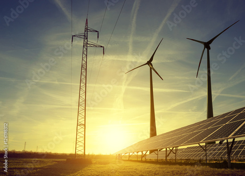 Photo Electricity transmission pylon with solar panels and wind turbines on field against the sunset