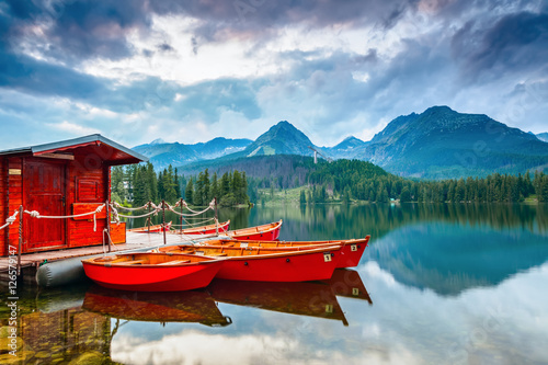 Boats stand near wooden bridge and a hut on a mountain lake.