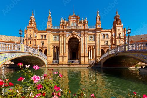 Fototapeta premium Hiszpania Square lub Plaza de Espana w Sewilli w słoneczny letni dzień, Andaluzja, Hiszpania. Klomby, mosty i kanał na pierwszym planie