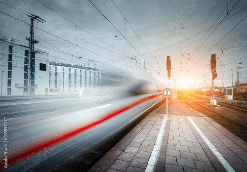 Wallpaper Mural High speed passenger train on railroad track in motion at sunset