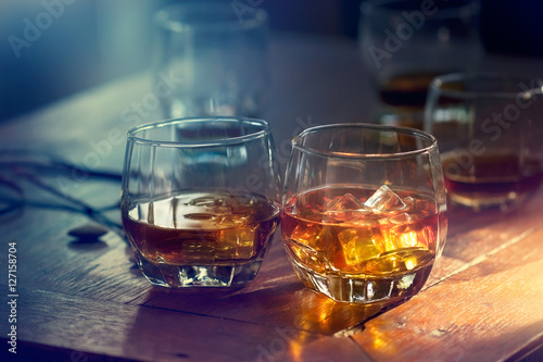 Slika na platnu Whiskey bourbon in a glass with ice on wooden table colorful background