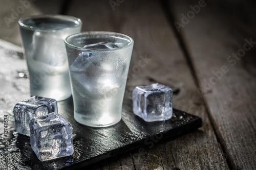 Obraz na płótnie Vodka in shot glasses on rustic wood background