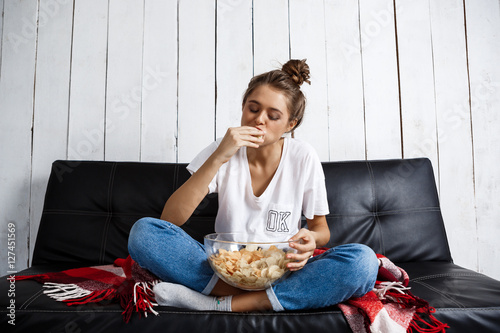 Photographie Beautiful domestic girl eating chips, watching tv, sitting at sofa