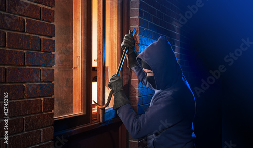 Fotografiet Burglar Using Crowbar To Break Into a House at night with room left and right fo
