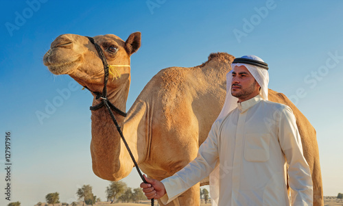 Fotografía Portrait of a young Arab with a camel in the desert