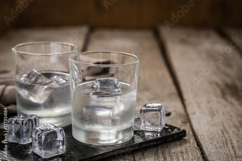 Fotografie, Obraz Vodka in shot glasses on rustic wood background