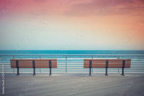 pastel toned beach boardwalk benches with ocean and sunset Fototapeta