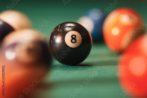 Fototapeta Pool ball with number 8 over green background.
