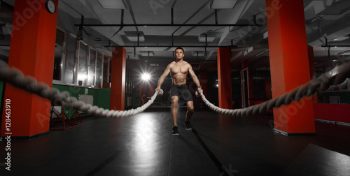 Fitness man working out with battle ropes at a gym