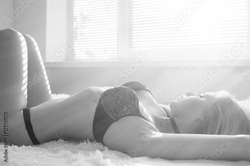 sensual girl in lingerie lying on fur in sun light, monochrome