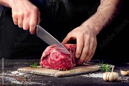 Fotografia Man cutting raw beef meat