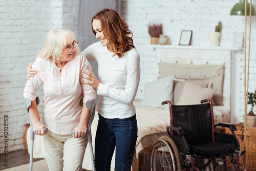 Fotografia Pleasant caring woman helping with rehabilitation her disabled grandmother