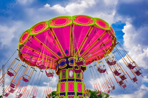 Colorful flying swing ride in motion at the amusement park Fototapete