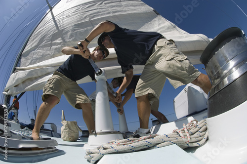 Leinwand Poster Low angle view of sailors operating windlass on yacht
