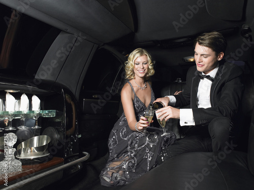 Canvas Print Happy young glamorous couple enjoying champagne in limousine