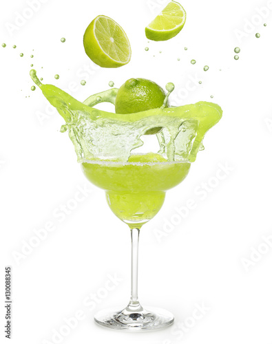 Fotografía lime falling into a margarita cocktail splashing isolated on white