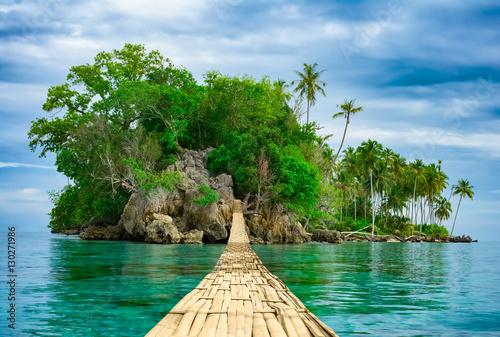 Bamboo hanging bridge over sea to tropical island