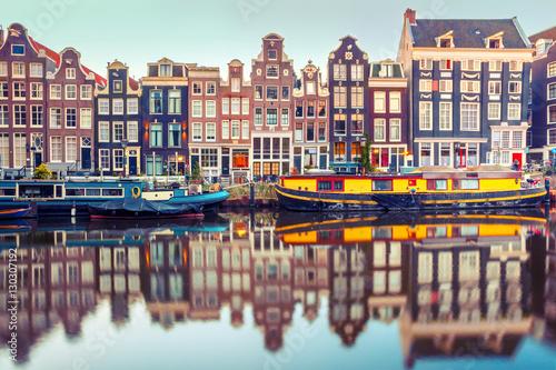 Fototapeta premium Kanał Amsterdam Singel z typowymi holenderskimi domami i łodziami mieszkalnymi w porannej niebieskiej godzinie, Holandia, Holandia. Używane tonowanie