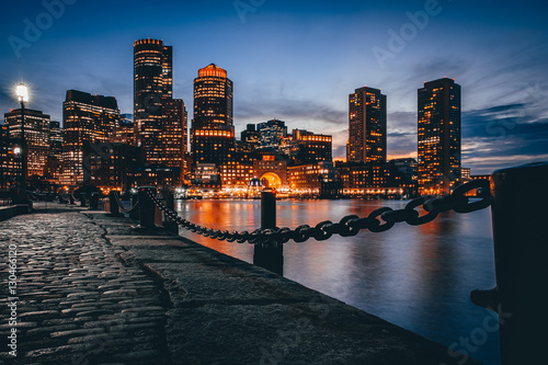 Photo Boston downtown skyline with skyscrapers over water at twilight