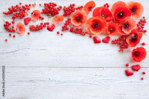 Red poppies, heart and berries on a wooden background