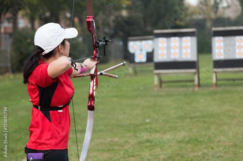 Canvas Print Female athlete practicing archery in stadium