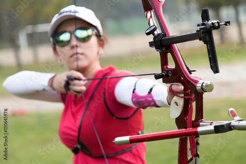 Leinwand Poster Female athlete practicing archery in stadium
