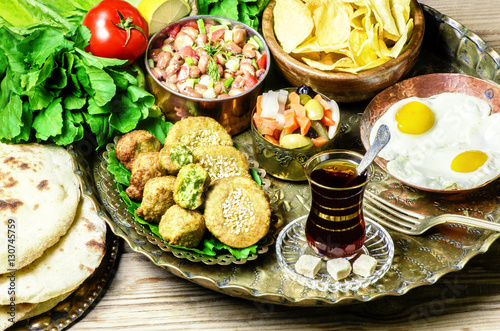 Arabic cuisine,Egyptian breakfast of fried egg, plate of flafel,beans,pickles,chips, fresh organic vegetables,traditional backing bread and cup of tea in copper tray..