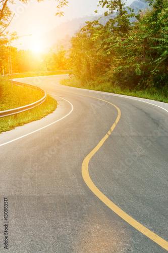 Obraz na plátne Asphalt road sharp curve along with tropical forest zigzag ahead with sun light