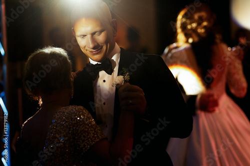 Obraz na płótnie Disco light shines over groom dancing with his mother