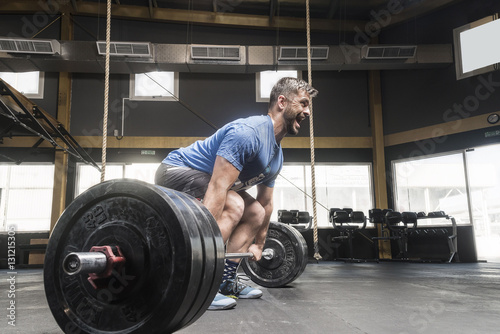 Strong white man deadlifts in crossfit box