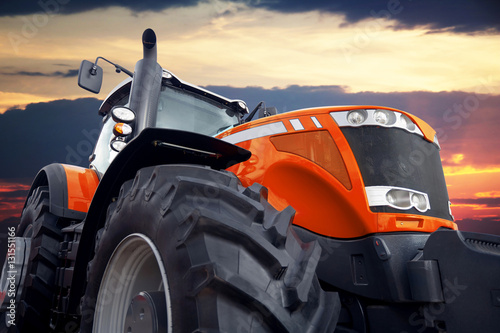 Canvas Print Tractor on a background cloudy sky