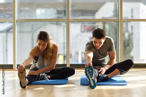 Obraz na płótnie Two people streching their legs in gym.