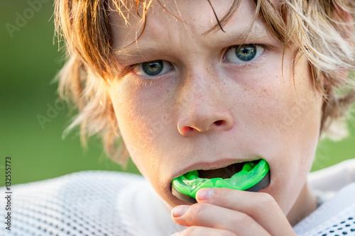 Fototapeta Boy putting in his mouth guard